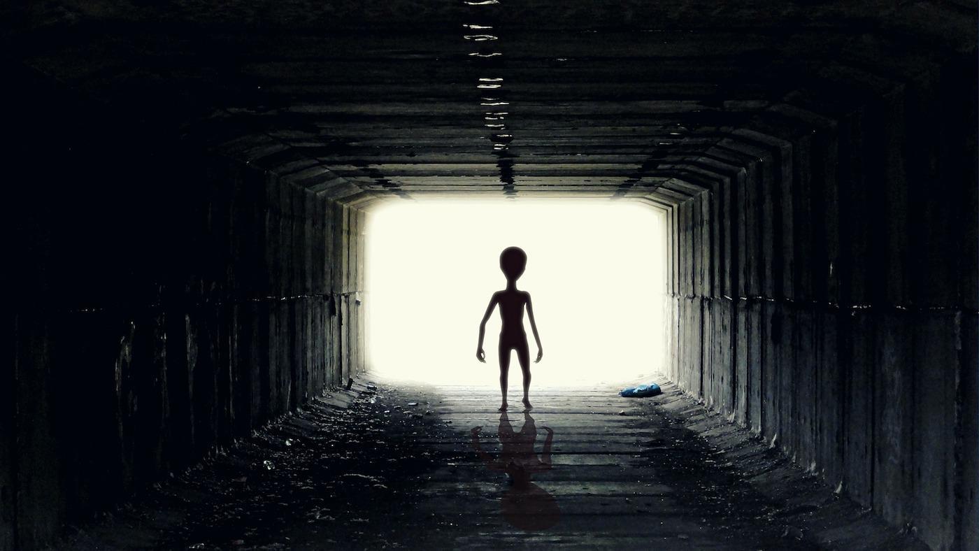 piccola figura aliena contro uno sfondo chiaro che cammina verso il tunnel